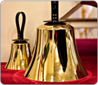 Closeup photo of two English handbells, bell end faceing down,  on a red cushioned surface