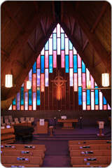 Guildwood Church sanctuary with stained glass windows, lights, peaked wooden ceiling, purple carpeted chancel