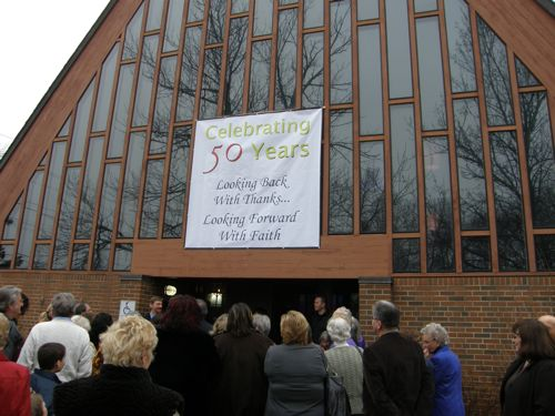 celebratory banner affixed to the outside windows of at the front entrance to a church