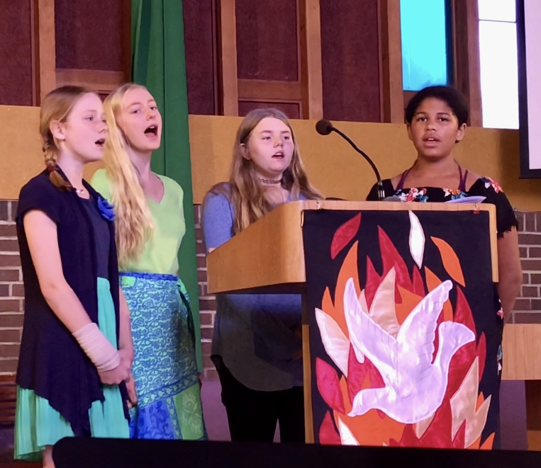 Four girls singing in front of a pulpit at a Sunday church service.