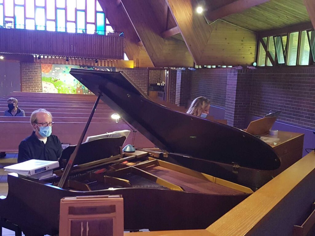 Woman at at organ next to man at a grand piano playing a duet in a church at a service