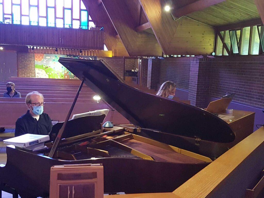 Woman at at organ next to man at a grand piano playing a duet in a church at a service