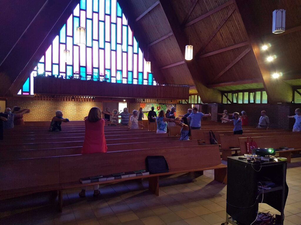 People in pews standing at a church service with outstretched arms miming hugs