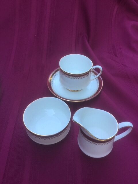 china coffee cup on saucer, with sugar bowl and creamer