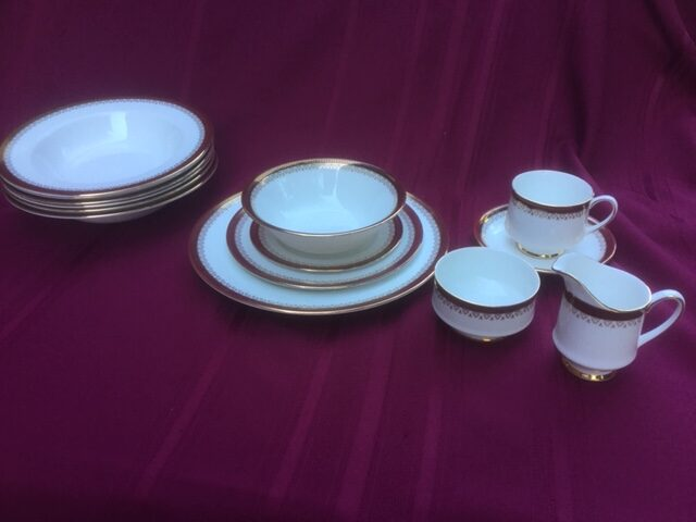 full set of fine china on a burgundy cloth background