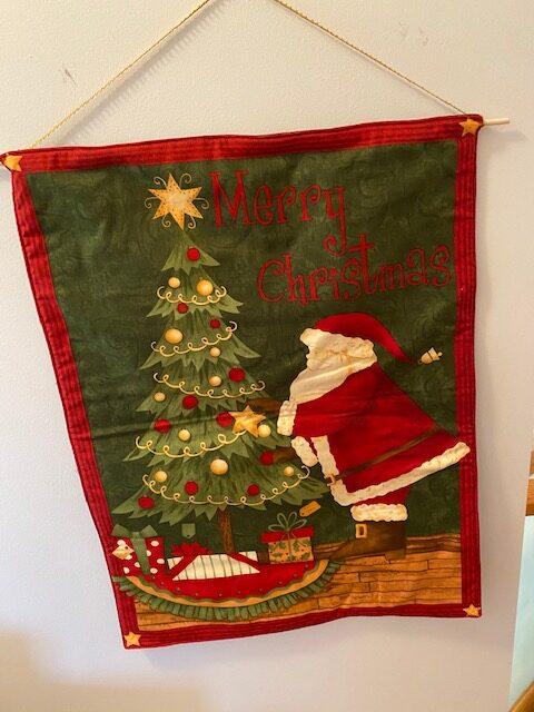 fabric wall-hanging depicting Santa Claus next to a Christmas tree