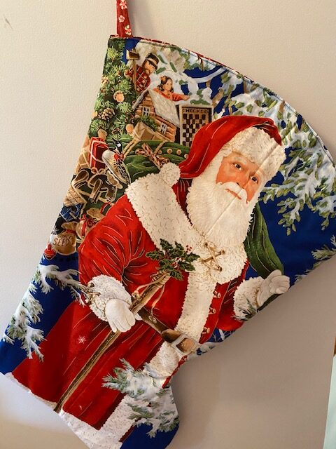 fabric wall-hanging that is an actual stocking that can be filled, depicting a Santa Claus on a blue background