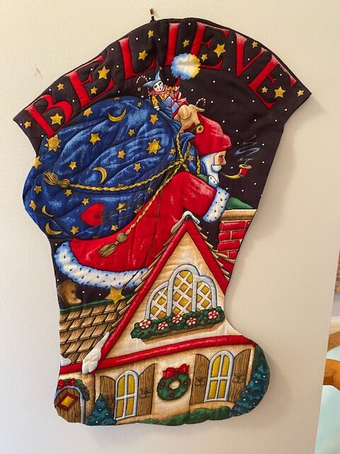 fabric wall-hanging depicting Santa Claus on a roof, shape of a stocking
