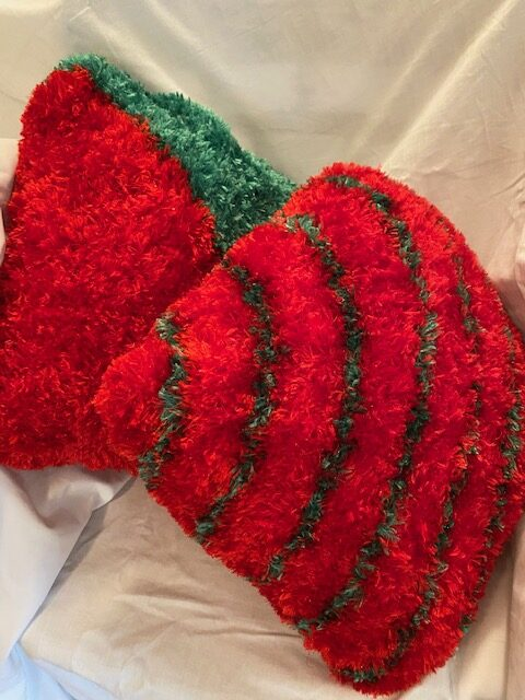 red fuzzy Christmas-themed cushions, one with green striped pattern at lower right and the other with a green fringe at upperleft