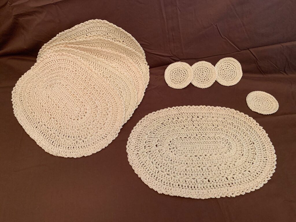 set of six white crocheted place mats with rounded corners shown as a set with one shown separately, along with a set of six white round crocheted coasters shown as a set with one shown separately