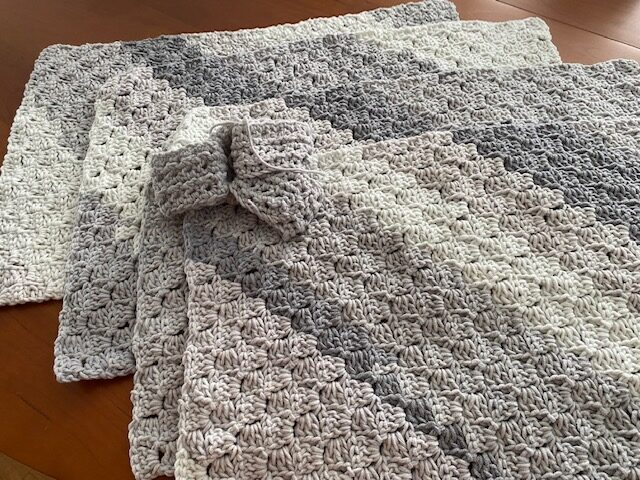 rectangular grey crocheted place mats shown with matching crocheted napkin rings