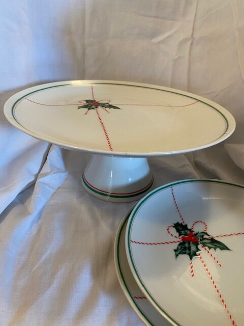 Christmas-themed cake stand upright, shown next to two dessert plates of the same patter, the latter only partially in view