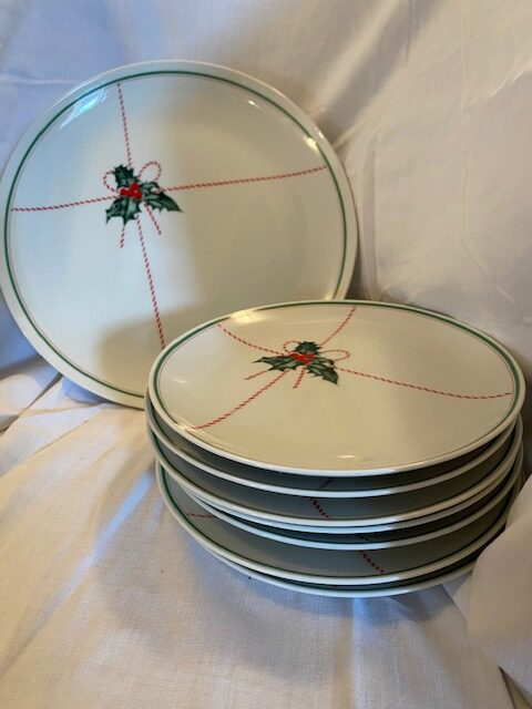 set of Christmas-themed dessert plates stacked with cake stand on its side