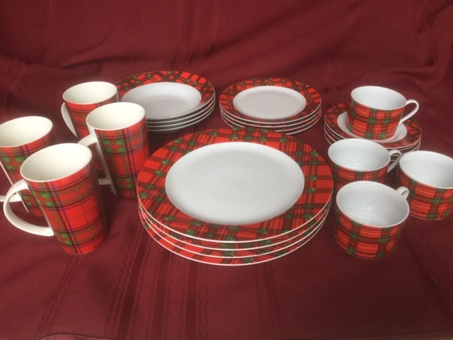 Trisa porcelain dinner set with dinner plates, side plates, soup bowls, cups and saucers, and mugs, with a geometric red and green Christmas tartan pattern