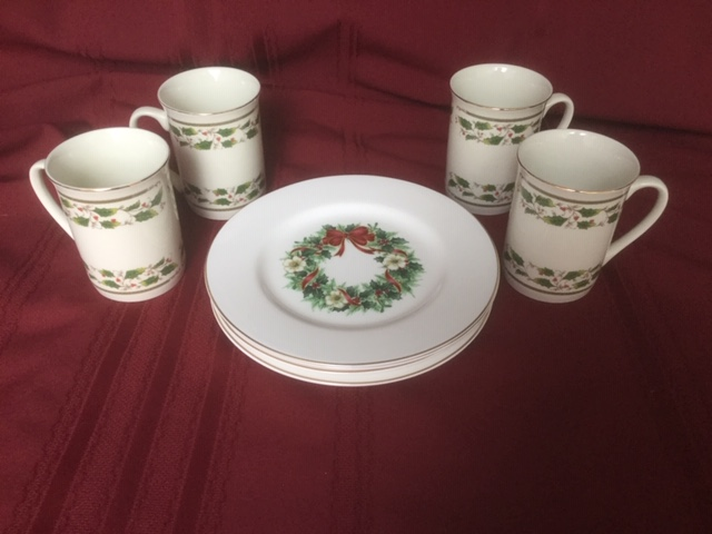 4 dessert plates and 4 mugs; plates with green red and white Christmas wreath on eating surface; and mugs with two rows of holly & berry pattern