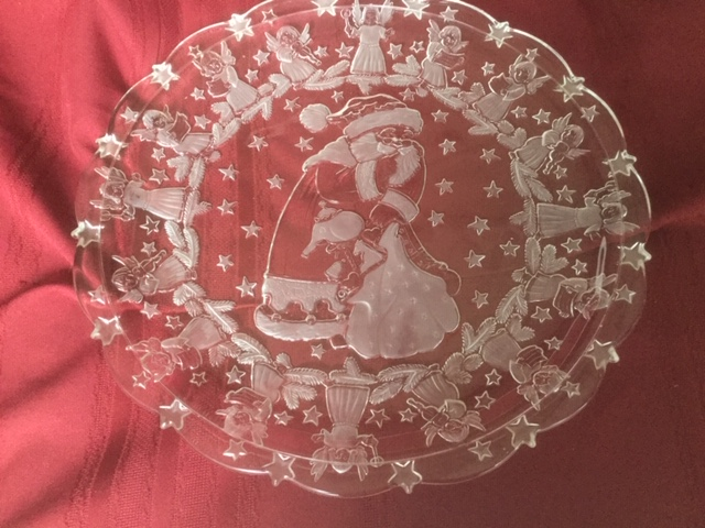 scalloped-rim clear glass circular presentation platter, with Santa Claus and stars on base, surrounded by angels and stars on the rim