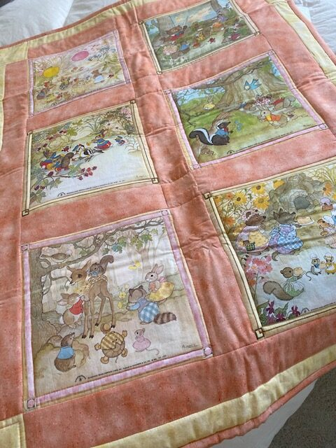 machine-quilted baby quilt with woodland creature scenes