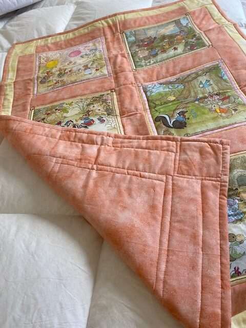 machine-quilted baby quilt with woodland creature scenes, turned up at one corner