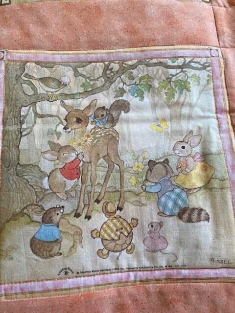Machine-quilted baby quilt with woodland creature scenes, close-up of one scene