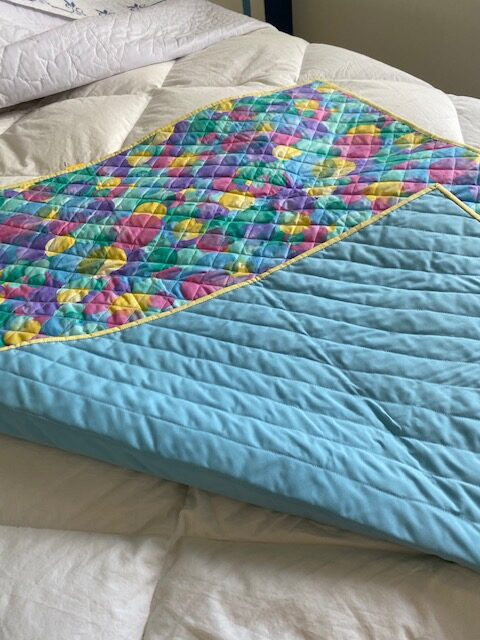 baby quilt – factory-quilted fabric with colourful geometric patterns, turned up at corner to reveal light blue underside