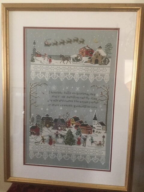 "framed needle-point artwork with village scene and text ""I heard the bells on Christmas day."""