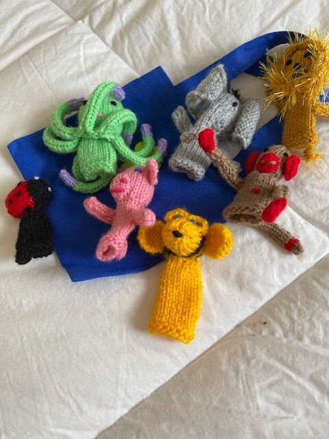 colourful crocheted finger puppets with blue fabric storage bag on white background