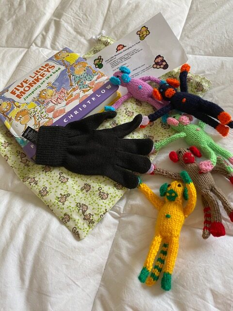 Five Little Monkeys book and game, with colourful crocheted monkeys and black glove