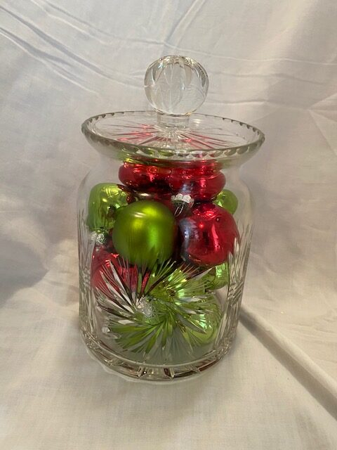 Round crystal serving dish with lid, filled with red and green Christmas balls