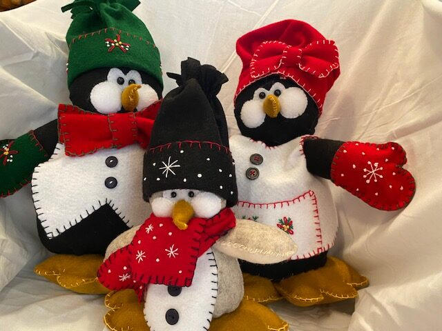 family of fabric penguins, with father, mother and child, wearing colourful Christmas clothing