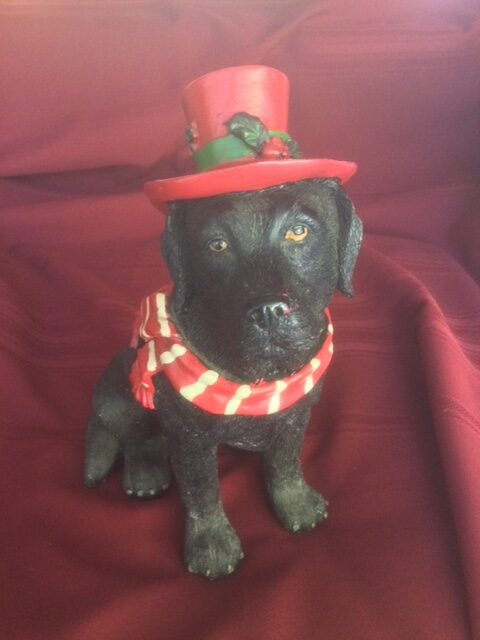 ceramic black Labrador dog with red and white scarf and red top hat
