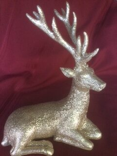golden sparkled resting deer figurine on a red background