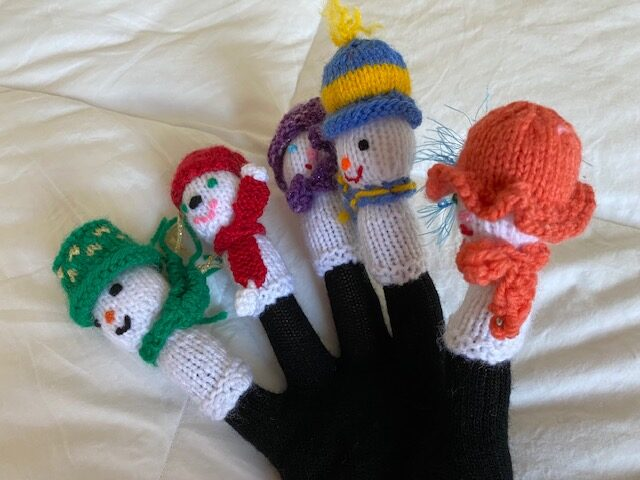 black snowman glove toy with different fabric characters on all five fingers