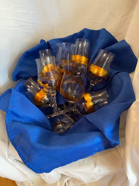 gift basket with 8 hand-painted wine goblets nestled among 8 blue fabric napkins, set on a white background