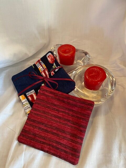fabric coasters, red and multi-coloured, with two red candles in low glass holders, all against a white background