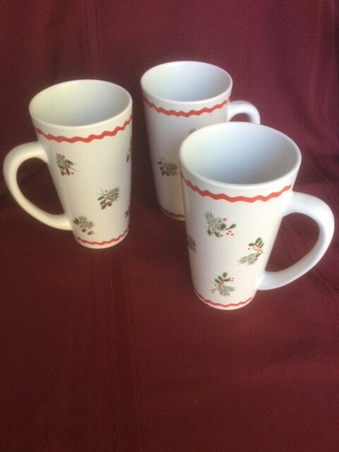 three tall white mugs each with two red ribbon stripes and a repeating holly & pine sprig motif