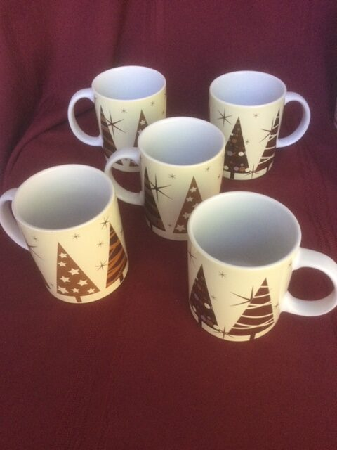 five white mugs with coloured Christmas trees and gold stars.