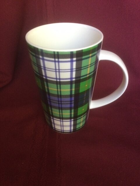 single tall mug with a green, blue, black yellow and white tartan pattern.