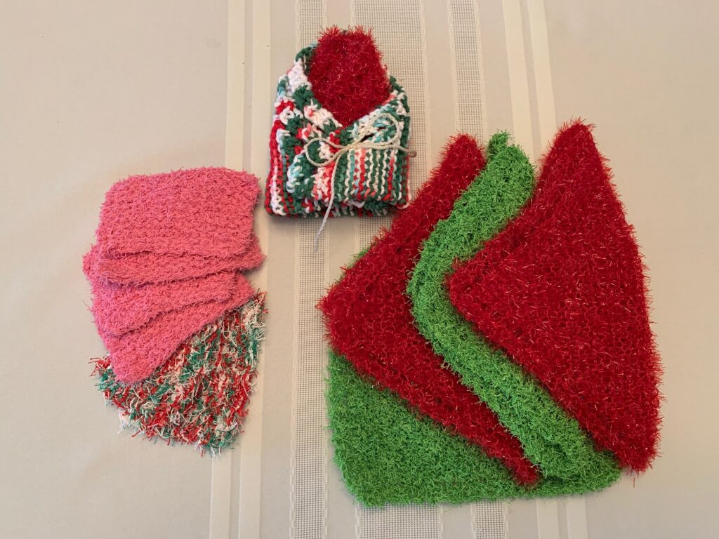 small nylon scrubbies in two patterns; large nylon scrubbies in two colours; one dish cloth wrapped around a medium scrubbie