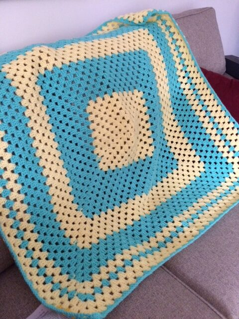 blue and yellow crocheted square afghan