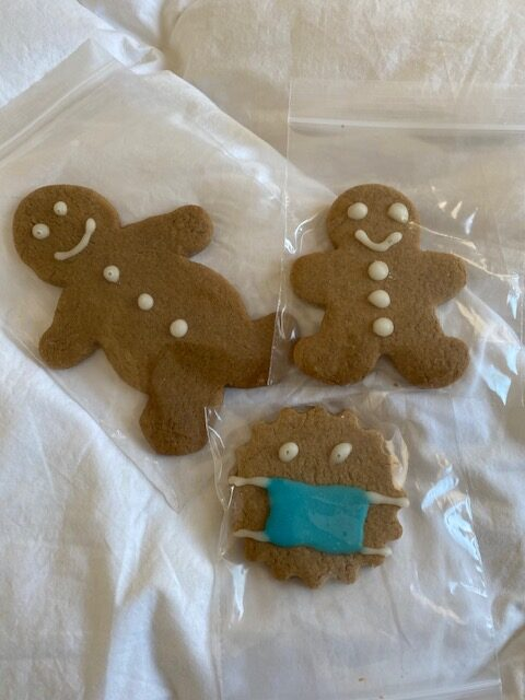 large and small gingerbread mean with white icing, round gingerbread cookie with hite icing ad coloured icing mask