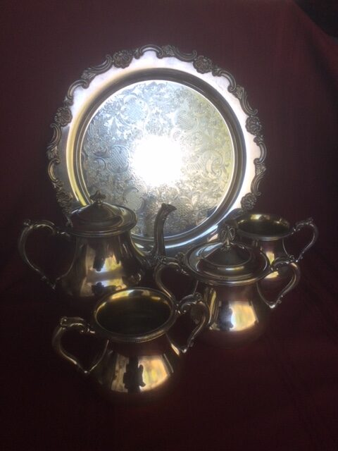 silver plate tea service with tea pot, creamer, two sugar bowls, and a tround tray, all with a grape pattern