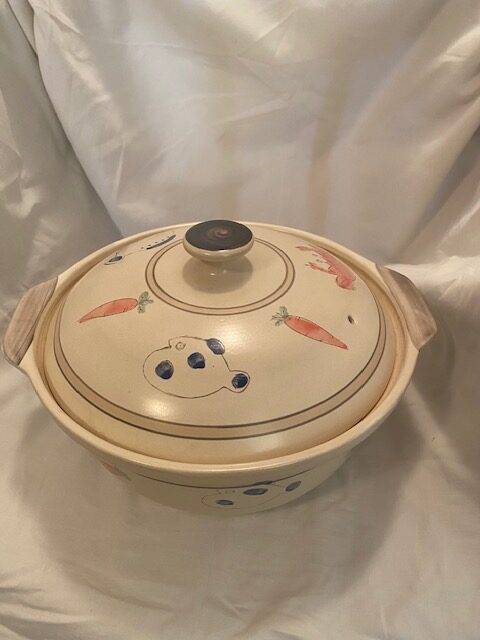 beige round casserole dish with colour images on lid and sides