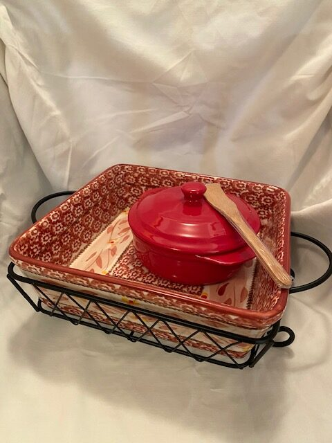 red patterned square casserole dish with black metal carrier; red brie baking dish with wooden knife
