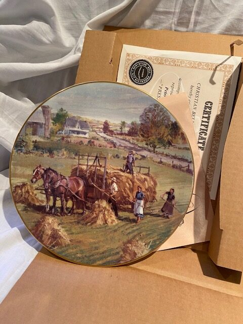 front of a collector plate - showing farm workers in a field and a horse-drawn wagon harvesting wheat