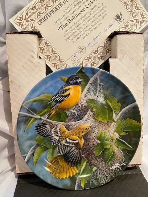front of a collector plate - showing two Baltimore orioles making a nest
