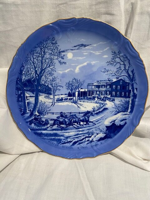 front of a collector plate - showing showing horses and sleighs and a country estate - blue and white coloration - Currier & Ives