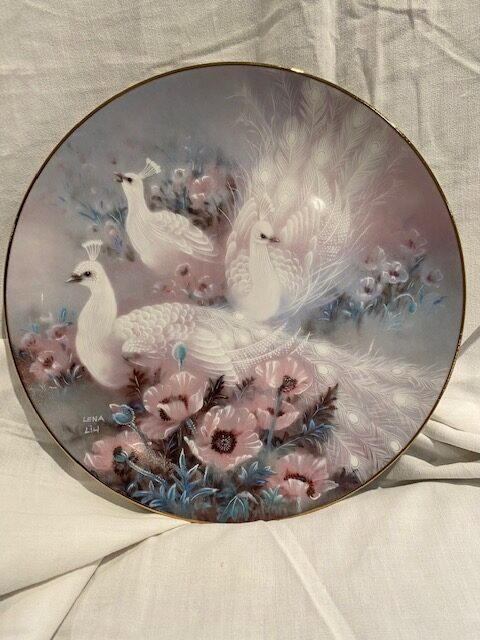 front of a collector plate - showing three peacocks in white among pink flowers
