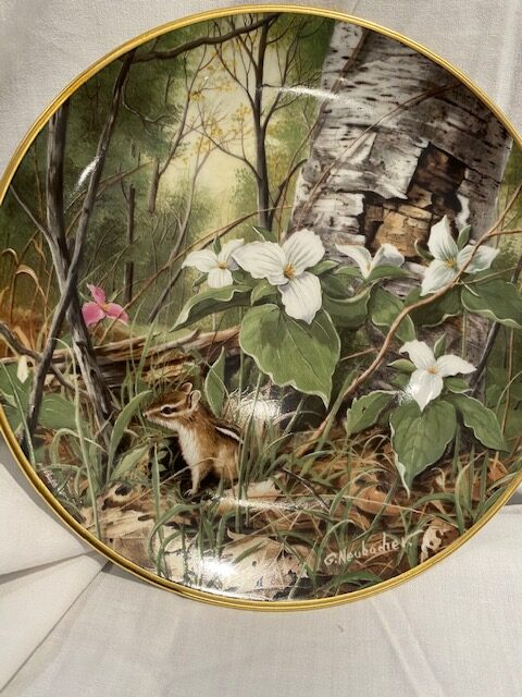 front of a collector plate - showing trillium flowers in white, one in pink, with a chipmunk in a forest scene