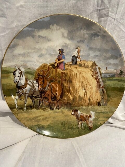 front of a collector plate - showing a horse-drawn hay wagon with a man and woman on top, a dog in the foreground, in a pastoral setting