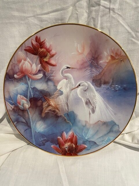 front of a collector plate - showing two white egrets against a background of red and white flowers and bluish leaves
